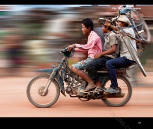 A typical village scene with 3 people riding on a motorcycle