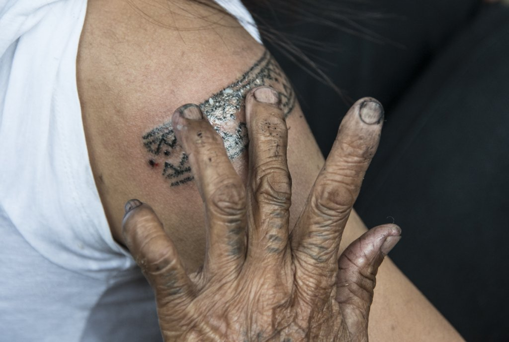 Rubbing some oil and ash mixture on the tatoo