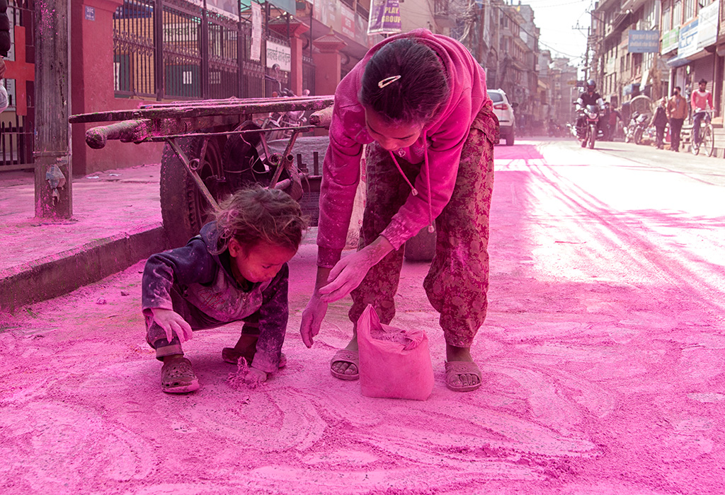 Children collecting colored powder on the roads