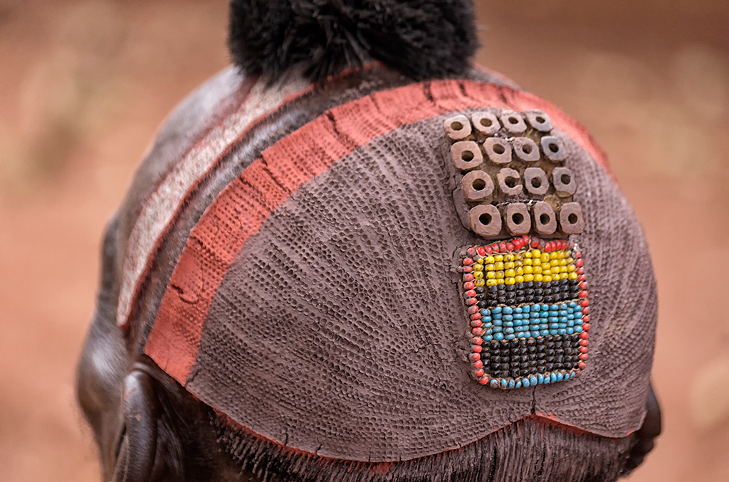 The Benna Tribal Chief's hairdressing is made from a mixture of clay and grounded hematite. Feathers are usually placed into the small 'ornaments' on their head during celebrations.