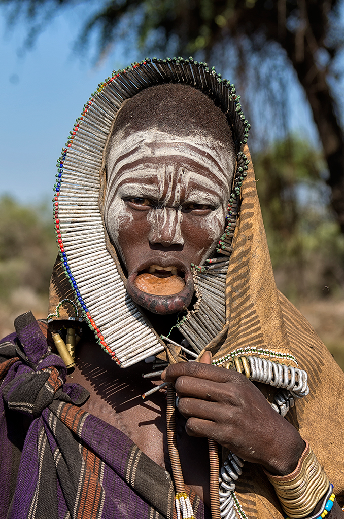 A Mursi woman with a small lip plate who will soon  progress onto inserting a six-inch plate into her lip